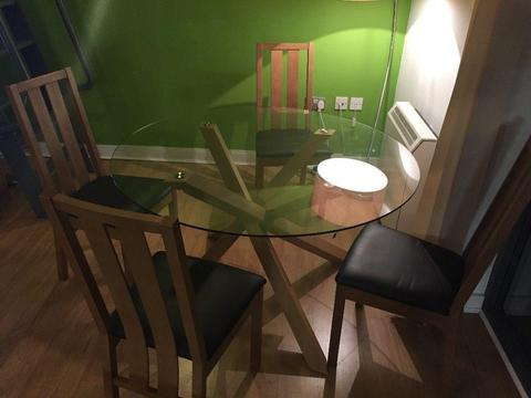 Contemporary circular glass dining room table with four chairs